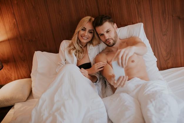 Szczęśliwa para w łóżku w domu i korzystać z telefonu komórkowego