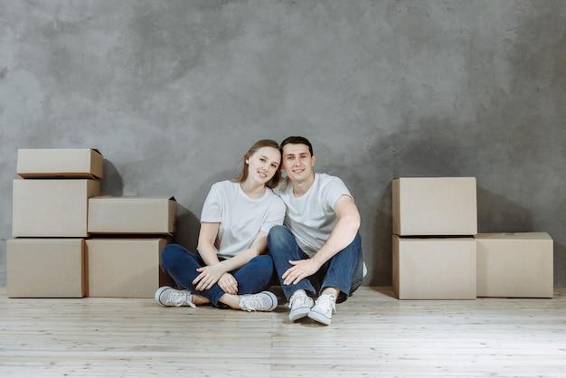 Szczęśliwa para w nowym domu. mężczyzna i kobieta siedzą na podłodze w pokoju pośród skrzynek z kortonem.