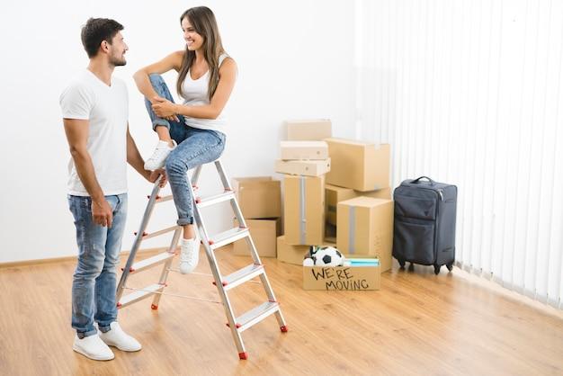 Szczęśliwa para w pobliżu drabiny na tle kartonowych pudeł
