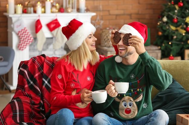 Szczęśliwa para w santa kapelusze, picie gorącej czekolady i jedzenie ciasteczek w domu