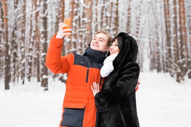 Szczęśliwa para w zimie robienia sobie zdjęć smartfonem.