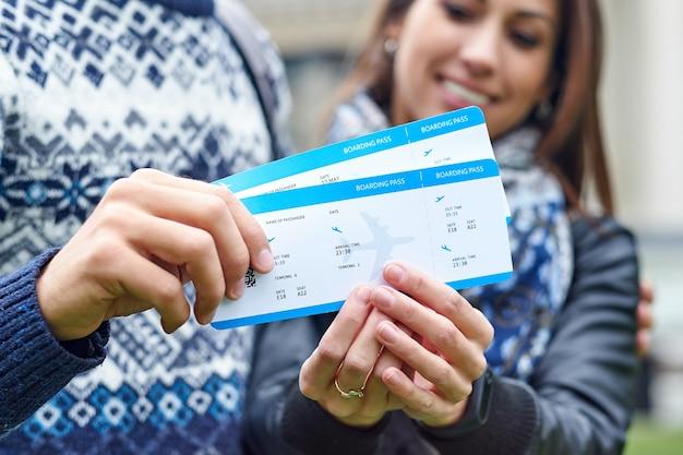 Szczęśliwa para wesoły przytulanie i pokazując bilety latające. mężczyzna robi kobiecie niespodziankę - daje bilety na miesiąc miodowy.