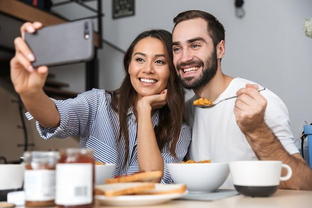 Szczęśliwa para wieloetniczna, jedząc śniadanie w kuchni, biorąc selfie