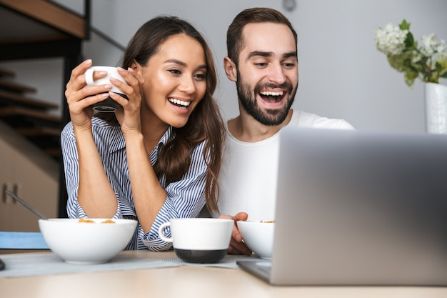 Szczęśliwa para wieloetniczne posiadające śniadanie w kuchni, patrząc na komputer