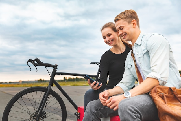 Szczęśliwa para wpólnie używa smartphone i ono uśmiecha się