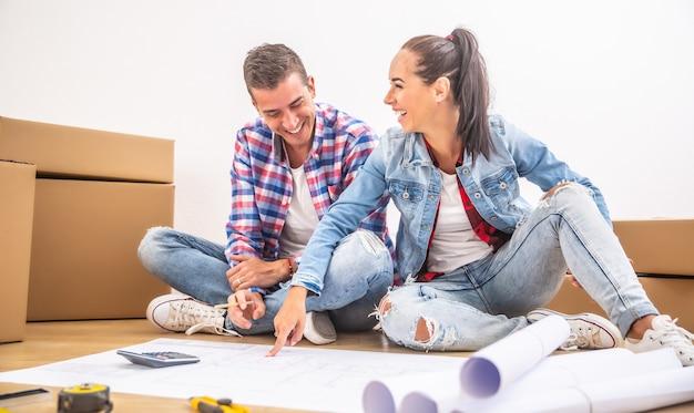 Szczęśliwa para wprowadziła się do nowego domu, bawiąc się przy planowaniu wystroju wnętrza.
