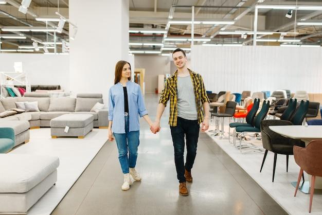 Szczęśliwa para wybiera meble w sklepie