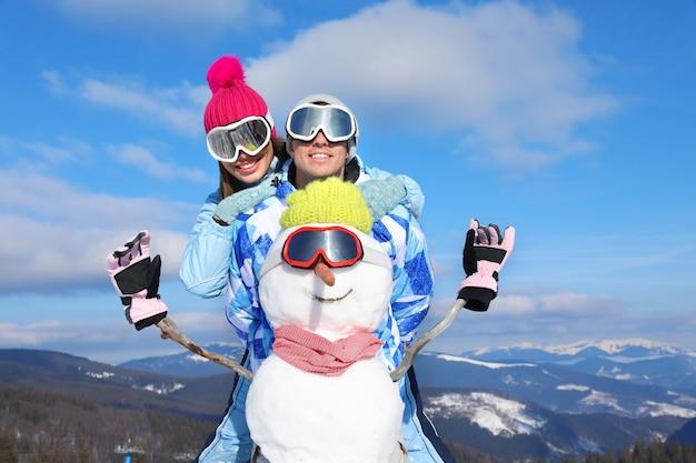 Szczęśliwa para z bałwanem w ośrodku narciarskim. ferie zimowe
