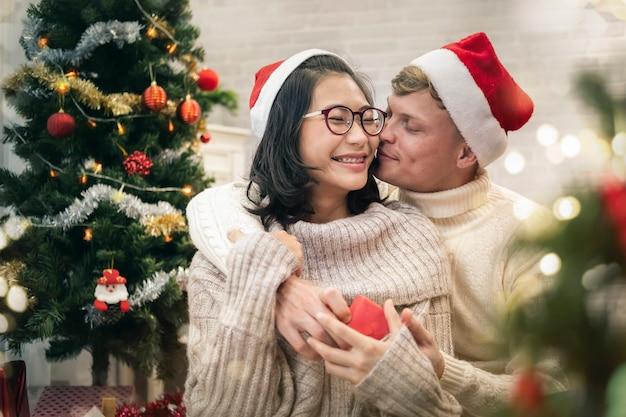 Szczęśliwa para z boże narodzenie teraźniejszości przytuleniem i obsiadaniem.