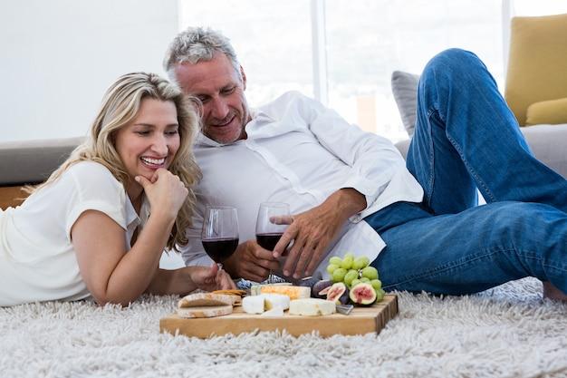 Szczęśliwa para z czerwonym winem i jedzeniem podczas gdy kłamający na dywaniku