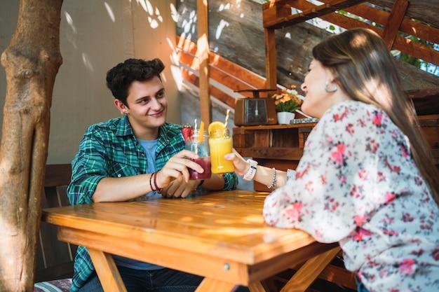 Szczęśliwa para z dwiema szklankami soku owocowego opiekania w barze - młodzi kochankowie patrzą sobie w oczy i uśmiechają się, ciesząc się randką.