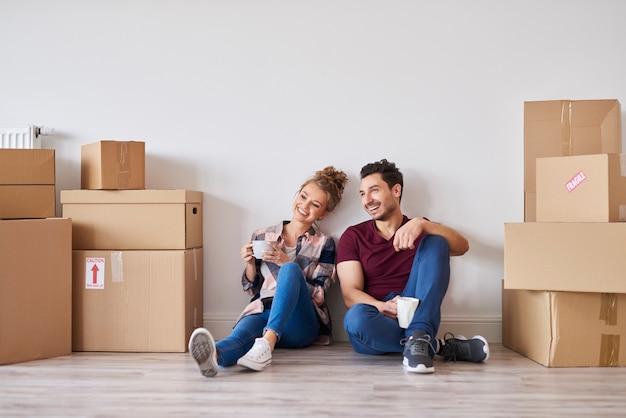 Szczęśliwa para z filiżankami kawy relaksuje się w swoim nowym domu