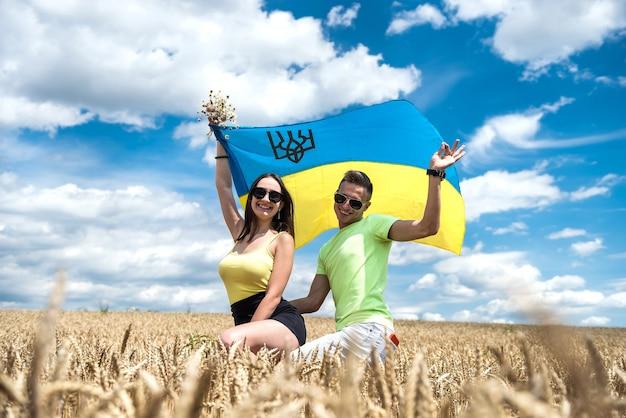 Szczęśliwa para z flagą ukrainy w polu pszenicy