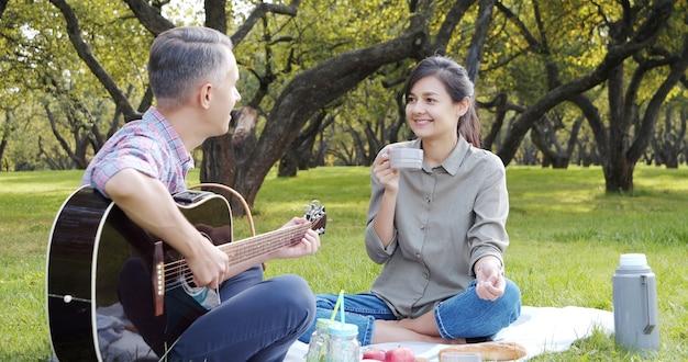 Szczęśliwa para z gitarą po odpoczynku na pikniku w parku na trawniku.