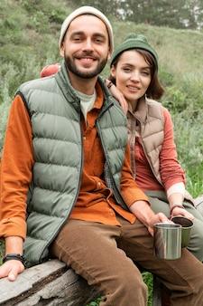 Szczęśliwa para z gorącymi napojami siedzi na dzienniku