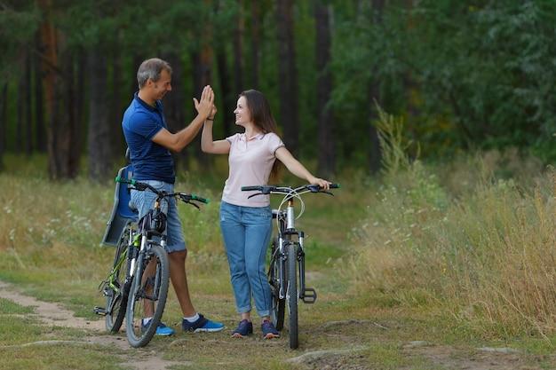 Szczęśliwa para z miłośników rowerów w sosnowym lesie, romantyczny spacer na rowerach. mężczyzna i kobieta z rowerami w parku, jazda na rowerze w letni dzień