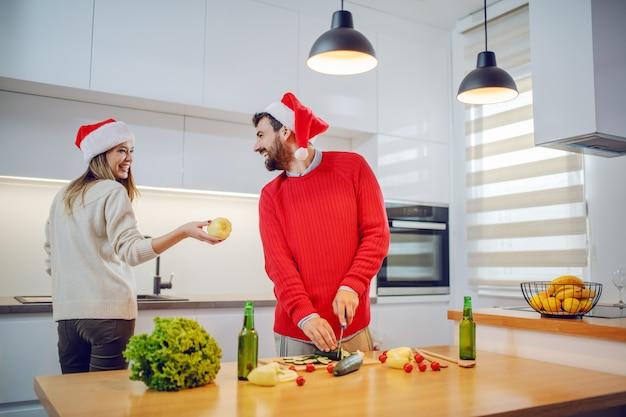 Szczęśliwa para z santa kapelusze na głowach przygotowuje zdrowe jedzenie na sylwestra