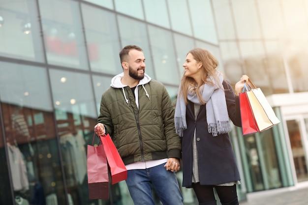 Szczęśliwa para z torbami na zakupy po zakupach w mieście uśmiechnięta i przytulająca