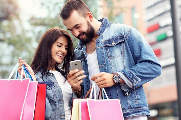 Szczęśliwa para z torbami na zakupy po zakupach w mieście