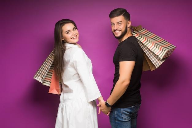 Szczęśliwa para z torbami na zakupy stojącymi blisko siebie z uśmiechem
