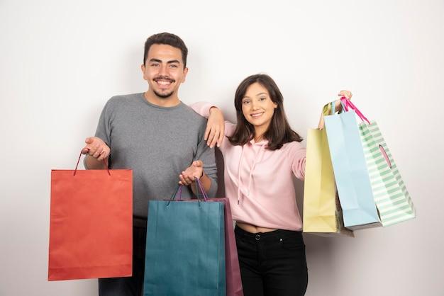 Szczęśliwa para z torby na zakupy, pozowanie na biały.