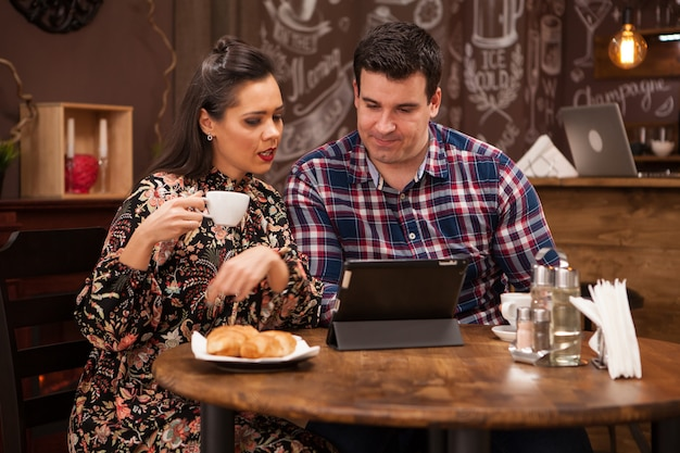 Szczęśliwa para za pomocą cyfrowego tabletu przy kawie w restauracji. hipsterska restauracja.