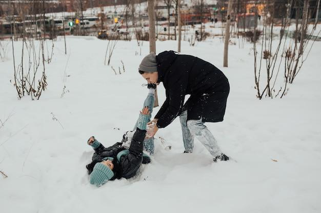 Szczęśliwa para zabawy podczas zabawy w walce na śniegu w parku miejskim