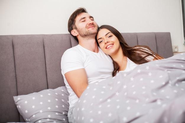Szczęśliwa para zabawy w łóżku. intymna, zmysłowa młoda para w sypialni bawi się sobą