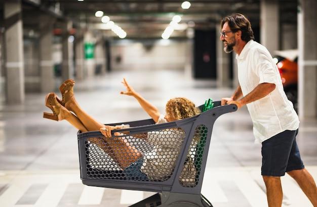 Szczęśliwa para zabawy z wózkiem na zakupy w garażu, mąż pchający beztroską żonę wewnątrz wózka na zakupy. para bawi się wózkiem w supermarkecie