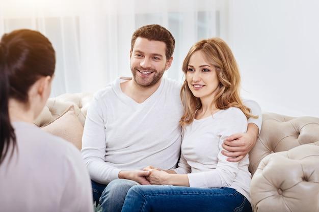 Szczęśliwa para. zadowolony szczęśliwy pozytywny mężczyzna patrząc na psychologa i uśmiechając się, przytulając żonę