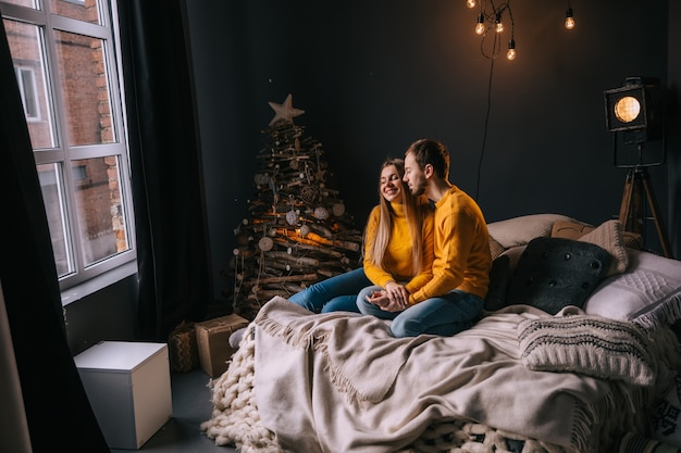 Szczęśliwa para zakochana leżąca w łóżku w sypialni z choinką i prezentami przy oknie