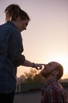 Szczęśliwa para zakochana na tle zachodu słońca zbliżenie. romantyczna randka w plenerze, delikatne biodrówki na pierwszym planie, żartobliwy nastrój