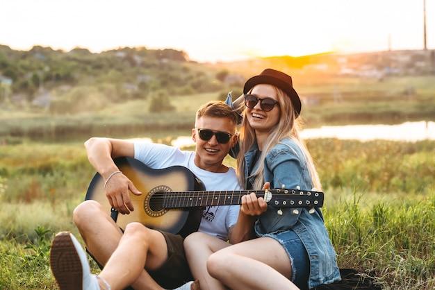 Szczęśliwa para zakochana w okularach przeciwsłonecznych, grająca na gitarze i ciesząca się o zachodzie słońca.