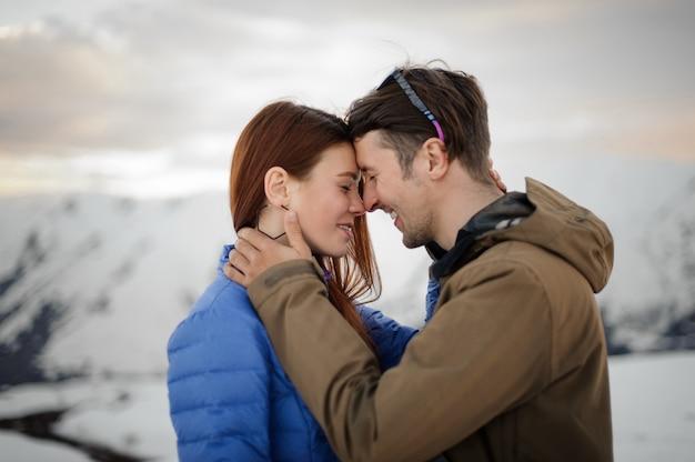 Szczęśliwa para zakochana w zimie delikatnie obejmuje w górach