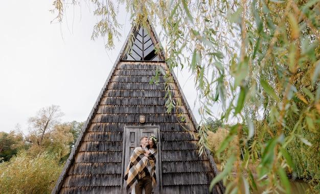 Szczęśliwa para zakochanych całuje się przed bajkowym drewnianym domem w środku parku