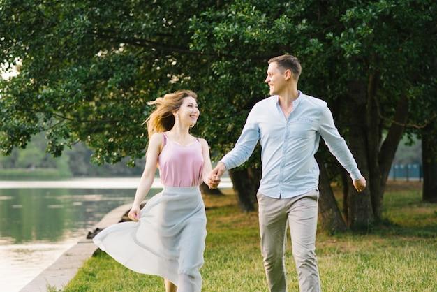 Szczęśliwa para zakochanych facet i dziewczyna biegną wzdłuż brzegu jeziora i trzymają się za ręce. walentynki. zabawny weekend i randka