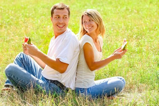 Szczęśliwa para zakochanych jedzenie arbuza na świeżym powietrzu w parku lato