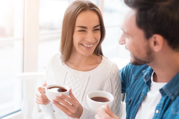 Szczęśliwa para zakochanych pije herbatę w domu lub kawiarni.