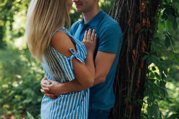 Szczęśliwa para zakochanych przytulanie na spacerze w zielonym parku. młody piękny mężczyzna i kobieta, zabawy i zabawy na łonie natury. koncepcja historii miłosnej na zewnątrz. romantyczna randka na świeżym powietrzu z bliska.