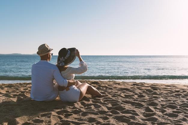 Szczęśliwa para zakochanych siedzi na plaży podczas zachodu słońca lub wschodu słońca.
