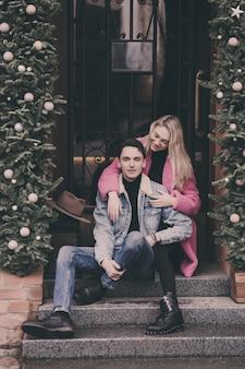 Szczęśliwa para zakochanych siedzi na schodach w mieście i uśmiechnięty.