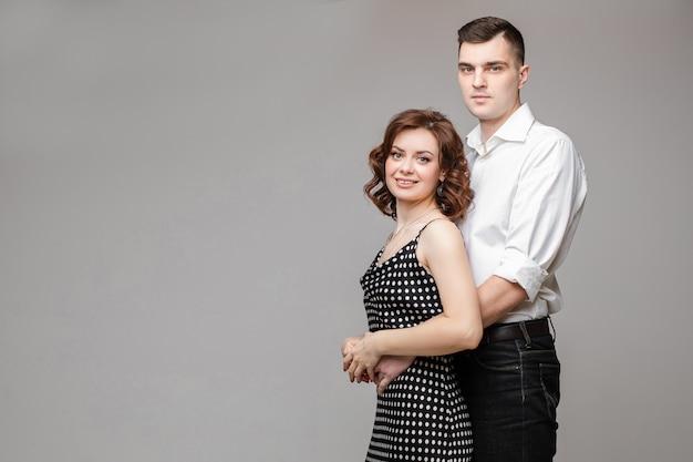 Szczęśliwa para zakochanych stoi i ściska razem, obraz na białym tle na czarnej ścianie