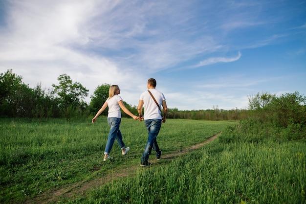 Szczęśliwa para zakochanych, trzymając się za ręce na spacerze w zielonym polu