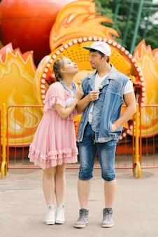 Szczęśliwa para zakochanych, zabawy w parku rozrywki, jedzenie lizaków