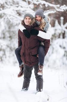 Szczęśliwa para zakochanych zimą w zaśnieżonym lesie, dziewczyna jeździ na grzbiecie ukochanego chłopaka, bawiąc się i uśmiechając
