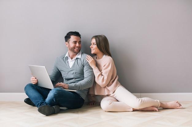 Szczęśliwa para zakupy online na laptopie siedząc na podłodze w domu.