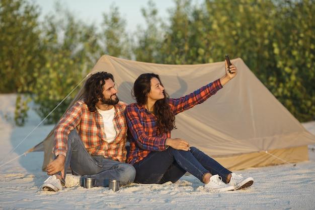 Szczęśliwa para ze smartfonem w obozie w pobliżu namiotu na zewnątrz