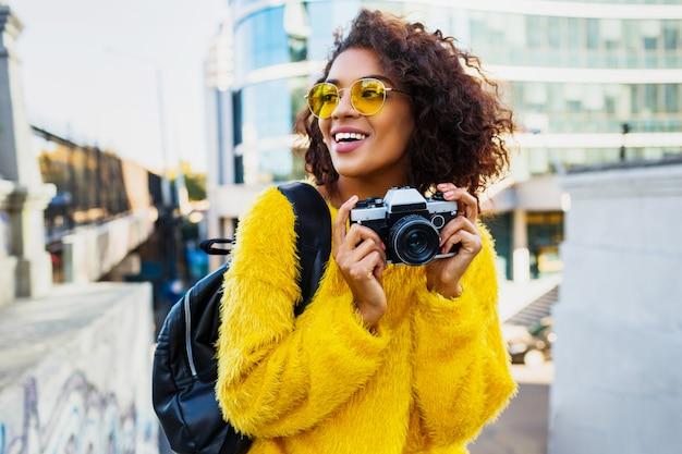 Szczęśliwa pewna kobieta trzymając aparat fotograficzny i spacery w dużym nowoczesnym mieście. +