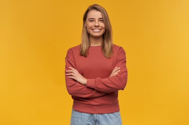 Szczęśliwa pewna siebie młoda kobieta w bluzie z terakoty i stojąc z rękami skrzyżowanymi na białym tle nad żółtą ścianą