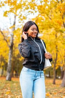Szczęśliwa piękna afroamerykanka modelka w modnych ubraniach na co dzień z modnymi niebieskimi dżinsami, kurtką i torebką w jesiennym parku ze złotymi jesiennymi liśćmi na zewnątrz